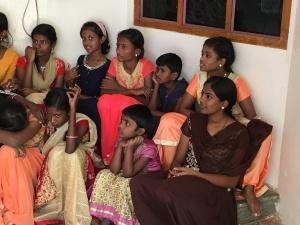 Mädchengruppe, an Wand sitzend